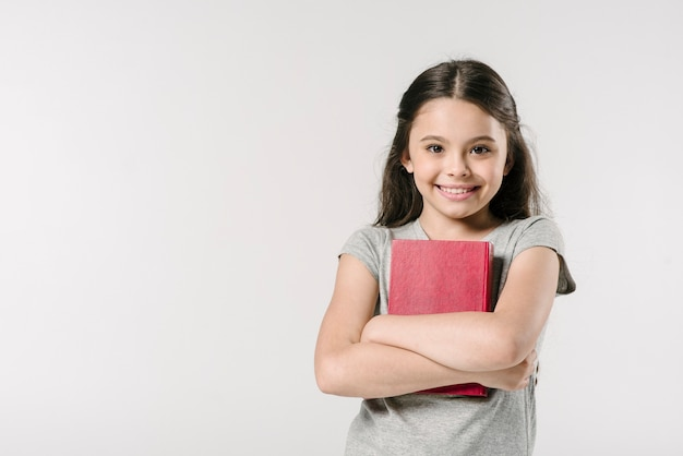 Sweet junior with book in studio Free Photo