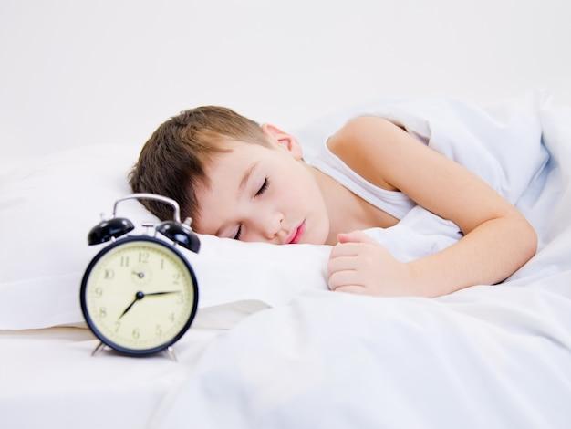 Милый ребенок спит с будильником возле его головы Бесплатные Фотографии