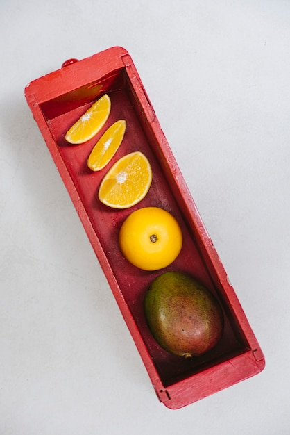 Sweet lime and mango in red wooden container Free Photo