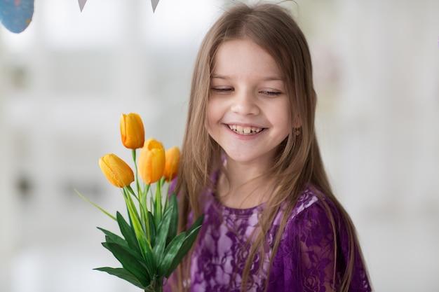 Sweet little dark hair girl in purple dress in studio with yellow tulips Premium Photo
