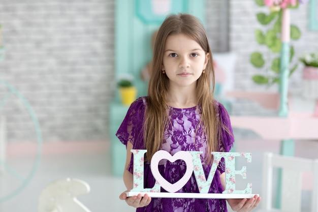 Sweet little dark hair girl in purple dress in studio Premium Photo