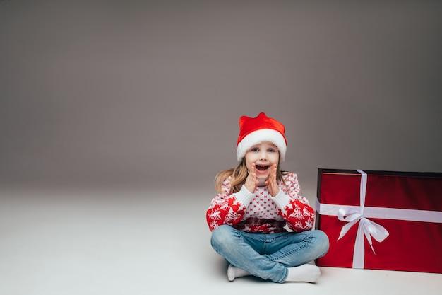 サンタの帽子とセーターを着たかわいい女の子がクリスマスプレゼントの隣に座って、口に手を当ててカメラに何かを発表しました。スペースをコピーします。 Premium写真