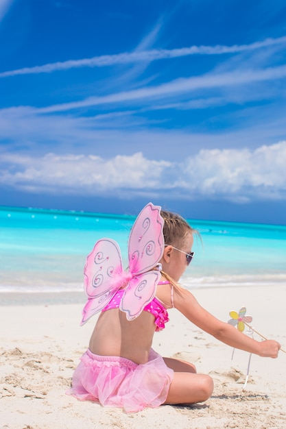 Sweet little girl with butterfly wings on white beach Premium Photo