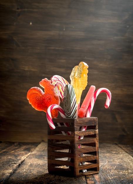 나무 스탠드에 달콤한 막대 사탕. 나무 배경. 프리미엄 사진