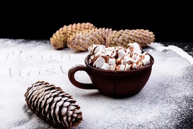 黒い背景に茶色のカップにチョコレートと甘いマシュマロ Premium写真