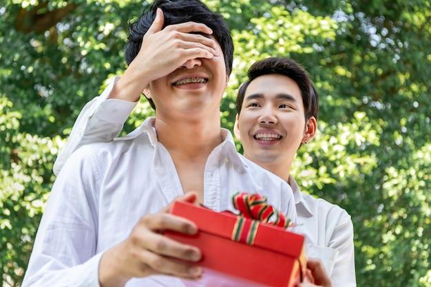 愛の甘い瞬間。アジアの同性愛者のカップルの抱擁と彼氏へのサプライズボックスギフト。コンセプトlgbtゲイ。 Premium写真