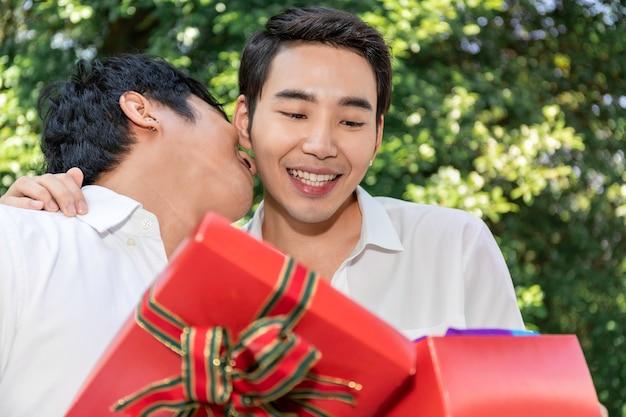愛の甘い瞬間。アジアの同性愛カップルの抱擁と彼氏へのサプライズボックスギフトの肖像画 Premium写真