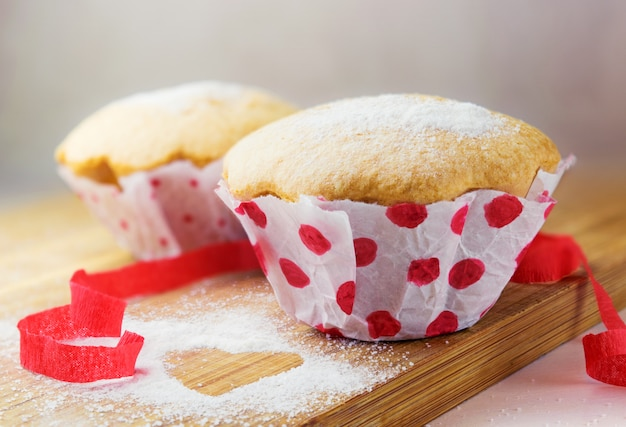 砂糖と赤いリボンの装飾が施された甘いマフィン 無料写真