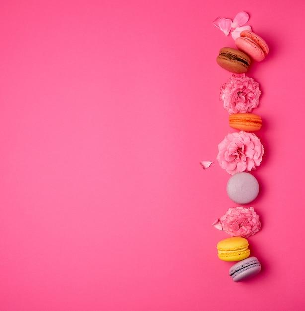 Сладкие разноцветные макаруны со сливками и розовым бутоном розы Premium Фотографии