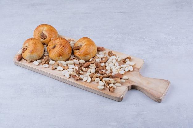 さまざまなナッツと木の板に穀粒が入った甘いペストリー。 無料写真