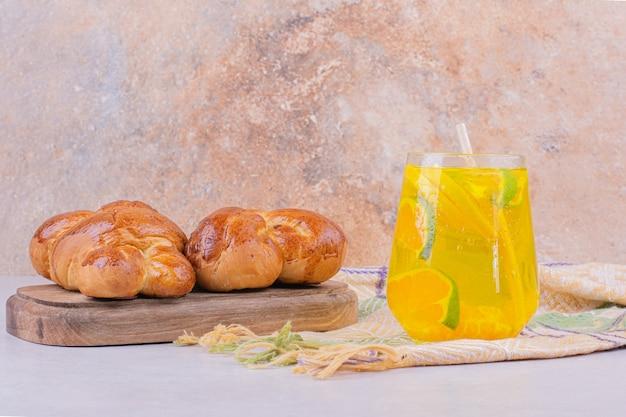 レモネードのガラスと木製の大皿に甘いペストリーパン。 無料写真