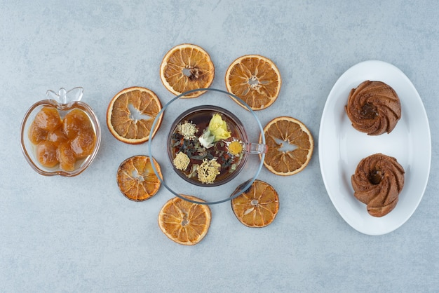 말린 오렌지와 대리석 배경에 허브 차 한잔과 달콤한 과자. 고품질 사진 무료 사진