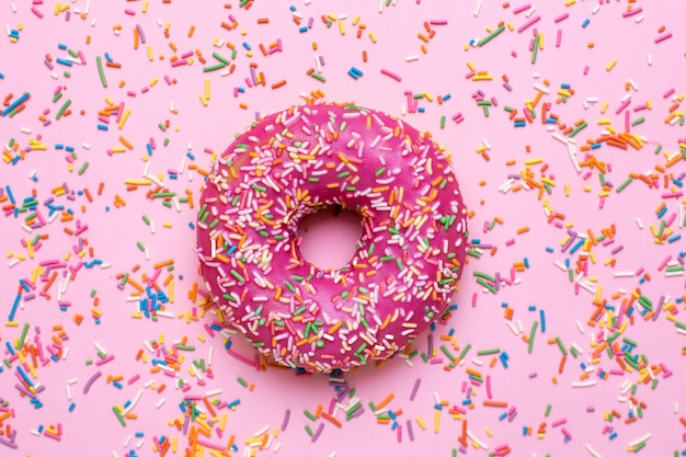Sweet pink donut with multicolored sprinkles on a pink surface flat lay Premium Photo