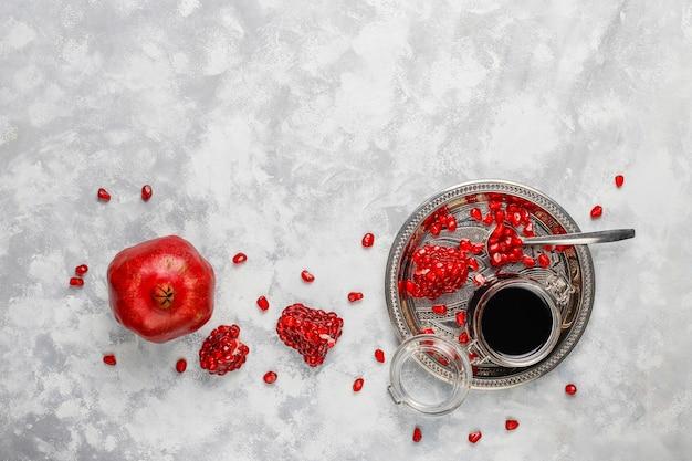 Сладкий гранатовый соус или сироп для мяса и рыбы под названием наршараб, в стеклянной банке с очищенным гранатом, селективный фокус Бесплатные Фотографии