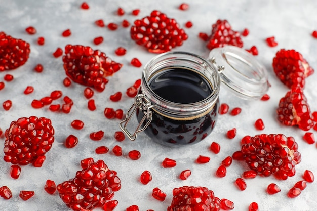 Sweet pomegranate sauce or syrup for meat and fish called narsharab, in a glass jar with purified pomegranate,selective focus Free Photo