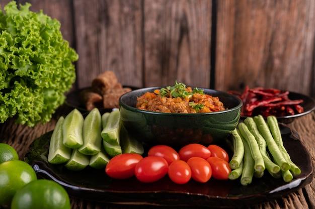 Сладкая свинина в черной миске с огурцами, длинной фасолью, помидорами и гарнирами Бесплатные Фотографии
