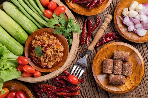 Сладкая свинина в деревянной миске с огурцом, длинной фасолью, помидорами и гарнирами. Бесплатные Фотографии