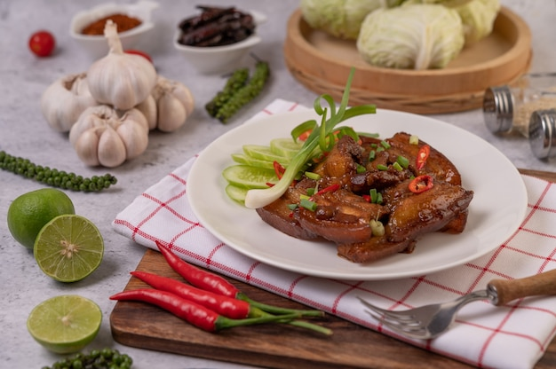 Carne di maiale dolce su un piatto bianco con scalogno tritato, peperoncino, lime, cetriolo, pomodoro e aglio. Foto Gratuite