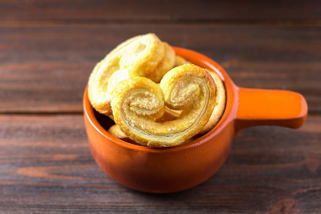 Sweet pretzels made of puff pastry in a bowl on a wooden table Premium Photo