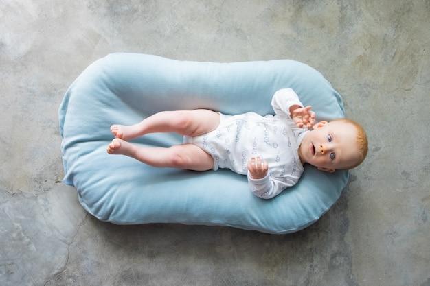 小さなマットレスの背中に横になっている甘い赤髪の赤ちゃん 無料写真