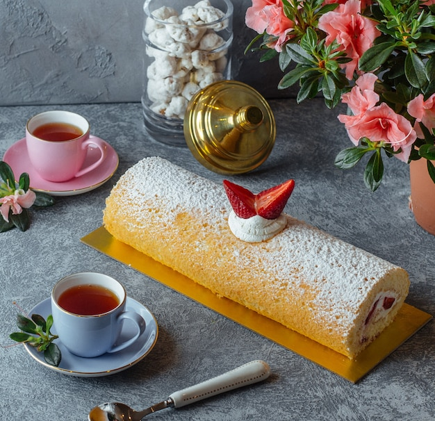 Sweet roulet with strawberry and black tea Free Photo