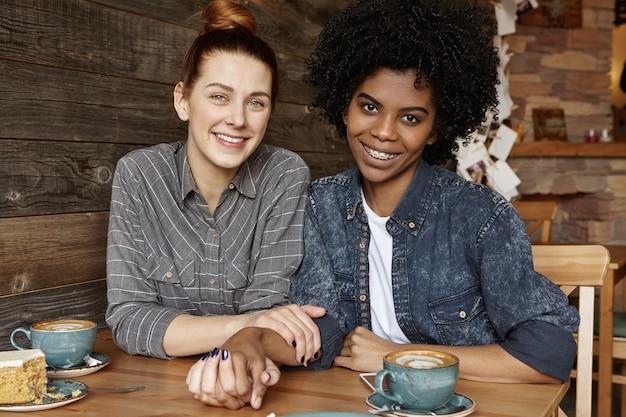 スタイリッシュなアフリカ系アメリカ人のガールフレンドと手を取り合って幸せな美しい白人赤毛の女性の甘いショット 無料写真