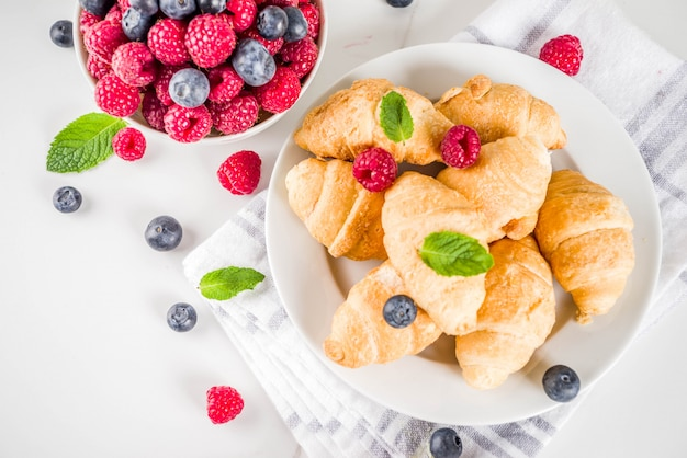 Sweet summer dessert, homemade baked mini croissants with berry jam, served with tea, fresh raspberries, blueberries and mint. on a white marble table,  top view Premium Photo