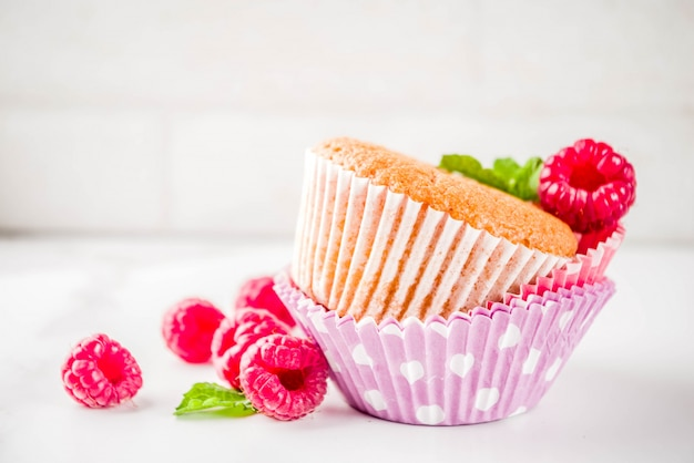 Sweet summer dessert, homemade baked muffin with raspberry jam, served with tea, fresh raspberries and mint. on a white marble table, Premium Photo