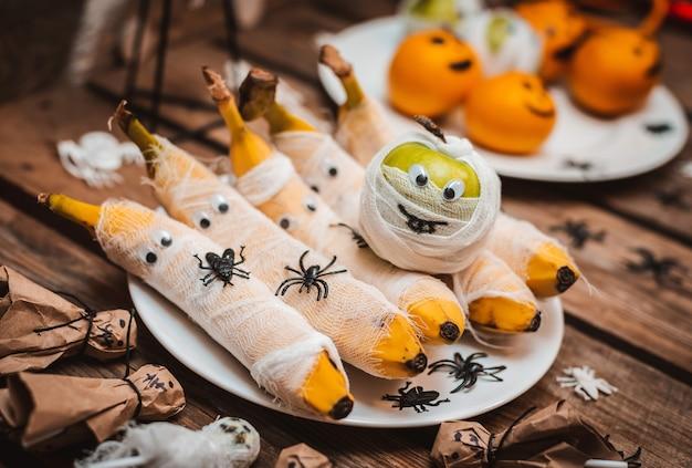 Сладкий стол с фруктами на хэллоуин. Premium Фотографии