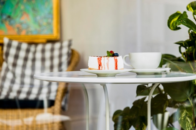 Sweet tasty cheesecake with berries and coffee cup on white cup in the coffee shop Free Photo