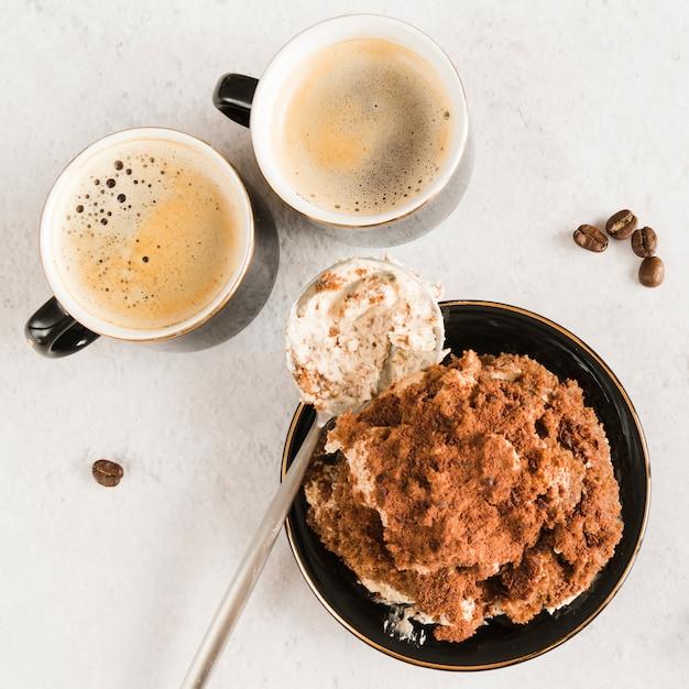 Sweet tiramisu on white table with coffee Free Photo