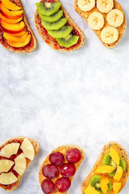 ピーナッツバター、いちごジャム、バナナ、ブドウ、ピーチ、キウイ、パイナップル、ナッツを含む朝食用の甘いトースト。コピースペース Premium写真