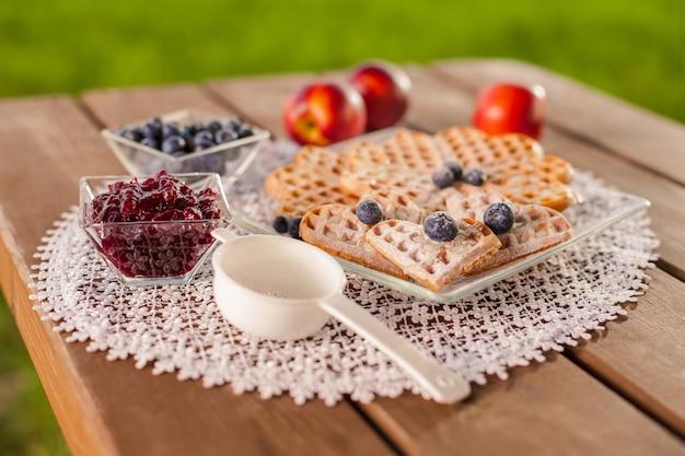 Сладкие вафли с фруктами в летний день на деревянном столе Бесплатные Фотографии