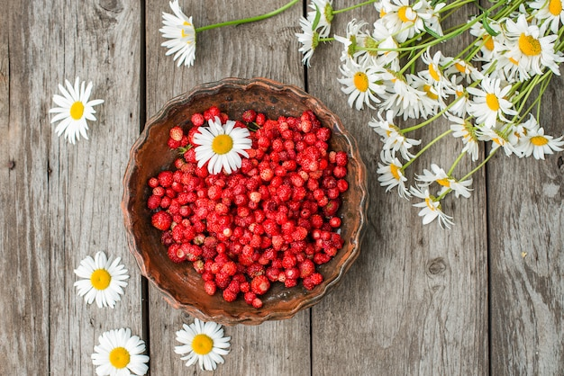 Sweet wild strawberries in plate with chamomile on wooden, top view. Premium Photo