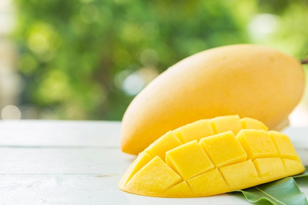 Sweet yellow mangos and slided on white wooden table on green nature Premium Photo