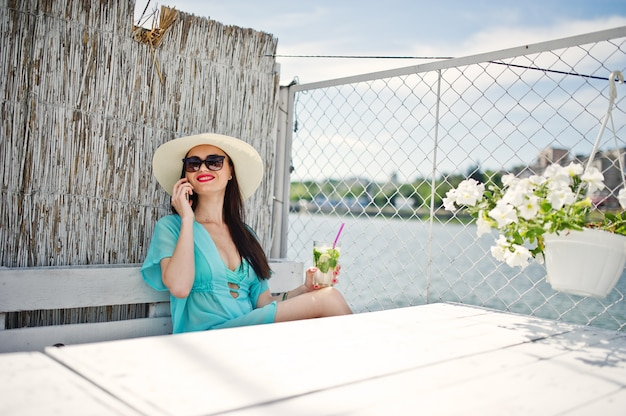 Sweet young lady wearing hat and sunglasses with a cocktail using her smartphone while sitting by the lake. Premium Photo