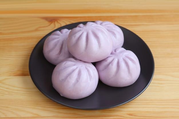 木製のテーブルで提供しています黒い皿に紫sweet蒸しパン Premium写真