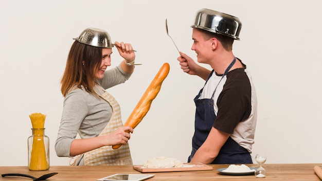 Sweethearts fooling around while cooking in kitchen Free Photo