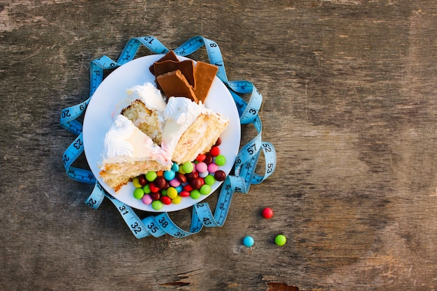 Sweets and measuring tape on table. Premium Photo