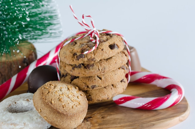 Sweets with christmas decorations and olive wood kitchen table. Premium Photo