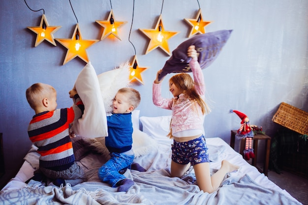 The sweety girl and boys playing and jumping on the bed Free Photo