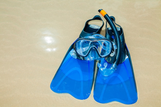 Swim flippers, mask, snorkel, hat in the surf on the sandy beach Premium Photo