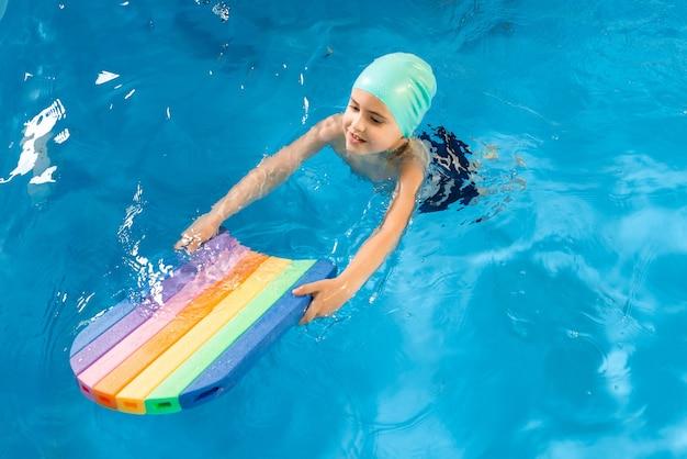 Урок плавания. крупным планом детей, практикующих флаттер-удар с доской в бассейне Premium Фотографии