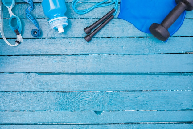 Swimming goggles; measuring tape; water bottle; skipping rope and dumbbells on wooden backdrop Free Photo