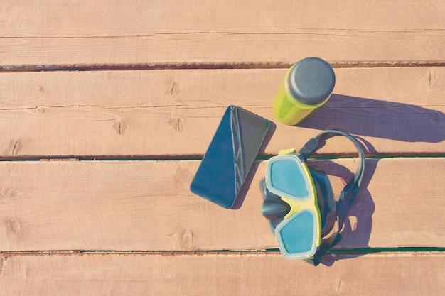 休日の晴れた日に木製テーブルに水泳マスク、スムージーとスマートフォンのボトル Premium写真