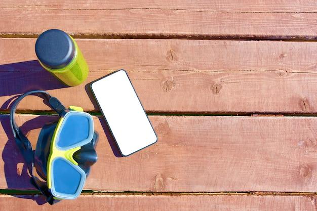 水泳マスク、スムージーのボトルと木製のテーブル上に孤立した画面とスマートフォン Premium写真