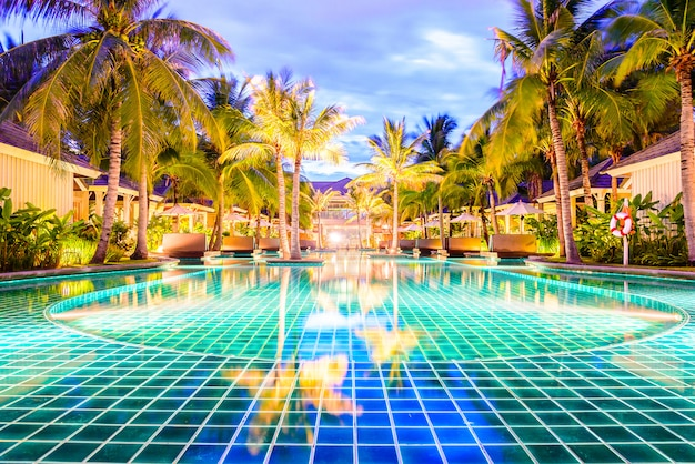Swimming pool with palm trees in resort hotel at night Free Photo
