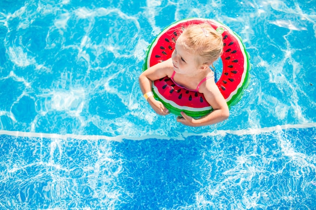 Swimming, summer vacation - lovely smiling girl playing in blue water with lifebuoy-watermelon. Premium Photo
