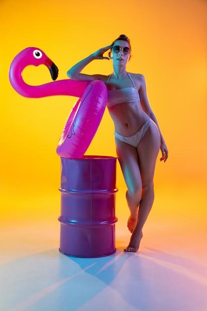 Фасонируйте портрет обольстительной девушки в стильных swimwear представляя на яркой желтой стене. лето, пляжный сезон Бесплатные Фотографии