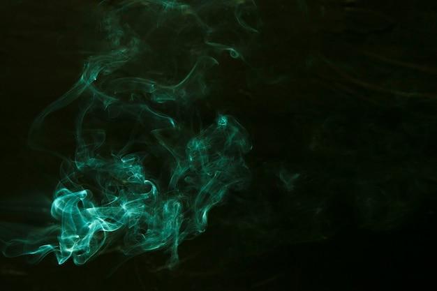 Swirl of green smoke on dark background Free Photo